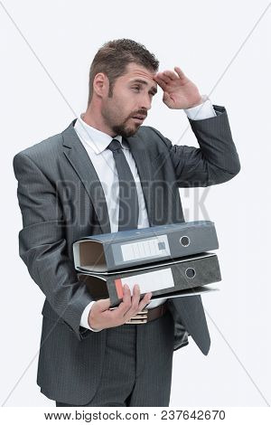 serious businessman holds a lot of folders with documents.