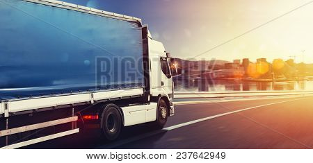 Moving Truck On The Highway With City Background