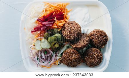 Falafel With Salad And Sauce In A Disposable Dish. Top View Of Chickpeas In A Plastic Container.