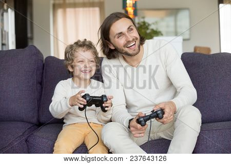 Happy Dad Laughing Playing Video Game With Excited Son At Home, Smiling Father Having Fun With Kid B