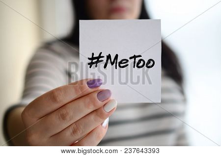 Young Sad Girl Shows A White Sticker. Caucasian Brunette Holding A Sheet Of Paper With Message. Meto