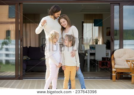 Happy Family With Kids Standing Outdoor Holding Keys Of Big Country House, Smiling Luxury Real Estat