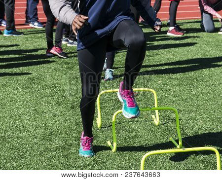 A High School Track And Field Team Is Doing Speed Work Working On Running Form Over One Foot Yellow