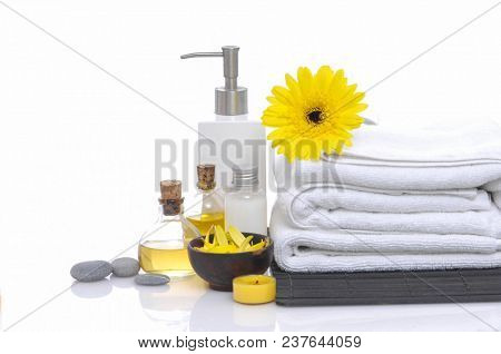 Spa setting with candle, towel , massage oil candle , yellow gerbera