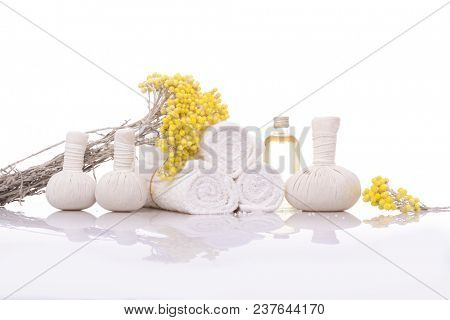 Spa setting with lying on yellow flower , herbal, ball ,rolled towel ,bottle oil