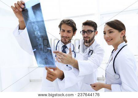 Three confident doctors examine an x-ray