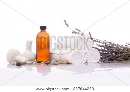 Spa setting with rolled towel, oil, stones