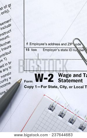 The pen, notebook and dollar bills is lies on the tax form W-2 Wage and Tax Statement. The time to pay taxes poster