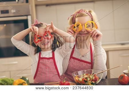 Beautiful Mother And Daughter Having Fun Making Salad In The Kitchen, Holding Pepper Slices As Glass
