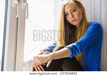 People and solitude concept. Alone sad troubled young woman long hair teen girl sitting on window sill lost in thought poster