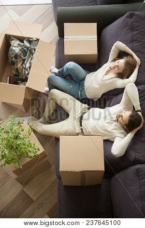 Happy Relaxed Couple Resting On Sofa Packing Unpacking Boxes, Young Renters Owners Enjoying Moving I