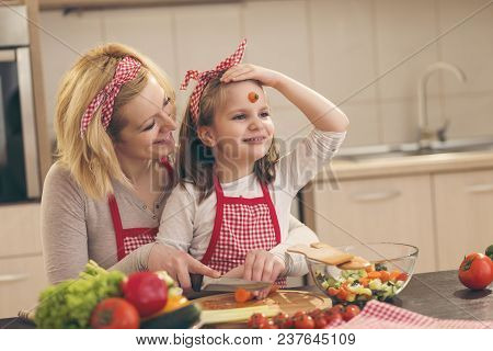 Mother And Daughter Having Fun While Cutting Vegetables And Making Salad