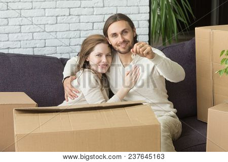 Portrait Of Happy Couple Holding Keys Embracing Sitting On Couch With Boxes In New Home, Smiling Ren
