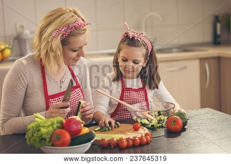 Mother And Daughter Cutting Vegetables And Making Salad. Focus On The Daughter