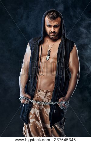 Athletic Handsome Muscular Man With Chain On Black Background With Smoke. Strong Soldier