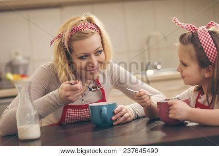 Beautiful Mother And Daughter In The Kitchen Having Breakfast, Eating Cereal. Focus On The Mother
