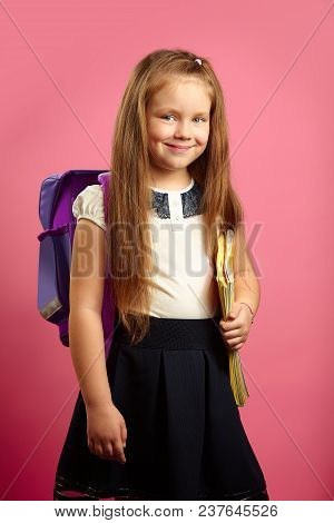 Portrait Of Schoolgirl With Backpack And Notebooks, Going To The First Class, Over Isolated Pink Bac
