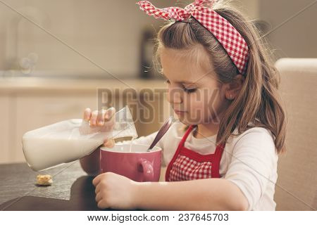 Little Girl Sitting In The Kitchen, Having Breakfast, Pouring Milk Into A Cereal Cup, Preparing Hers