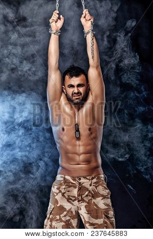 Athletic Muscular Man With Chain On Black Background With Smoke. Soldier In Captivity