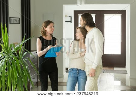 Friendly Realtor Or Landlord Talking Showing Modern Luxury House For Sale To Young Couple Customers,