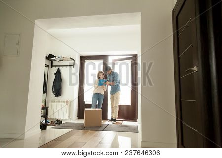 Young Woman Signing For Parcel Standing In House Hallway, Client Receiving Box From Courier At Home