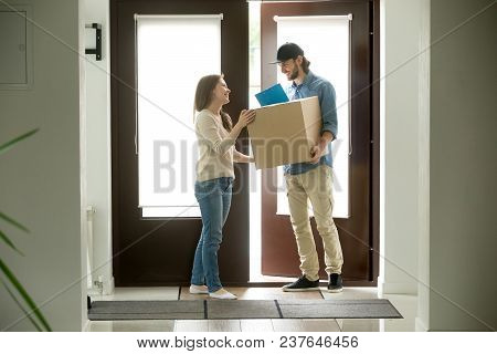 Happy Young Woman Receiving Parcel From Smiling Courier At Home, Delivery Man Holding Carrying Packa
