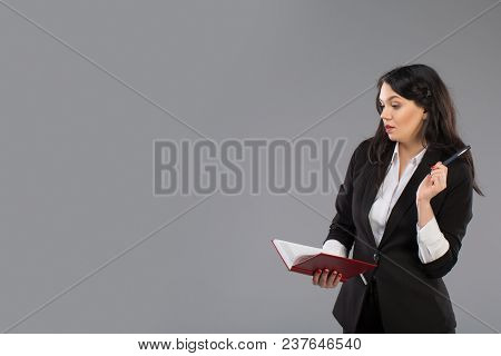 Young Business Woman With Notepad And Pen Close To Her Chin. Pensive Business Lady Writing On Clipbo