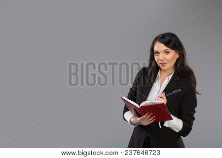 Young Business Woman Writing Down Notes To Notepad. Pretty Thoughtful Business Lady Writing On Clipb