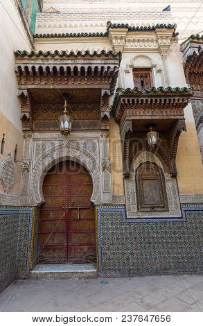 Traditional entrance gate with portal and ornaments, door and window, in Fes, Morocco poster