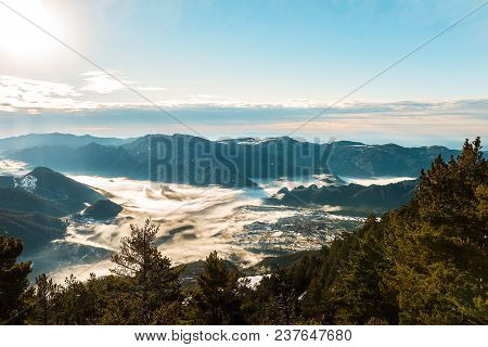 Back-lit View Of A Valley On A Winter Morning. The Cold Weather Makes The Fog Stay Between The Mount