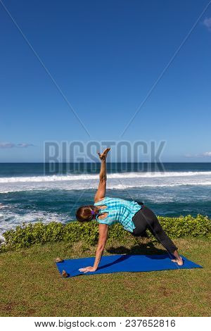 A Woman Practicing Her Yoga On The Scenic Island Of Maui