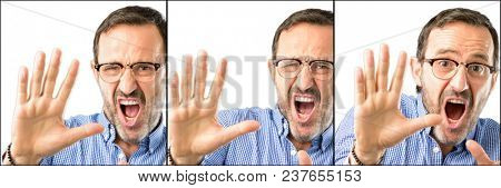 Middle age handsome man closeup disgusted and angry, keeping hands in stop gesture, as a defense, shouting