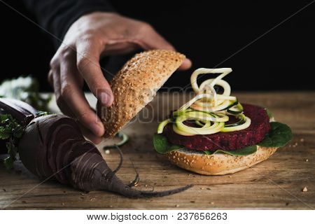 closeup of a young caucasian man preparing a beet burger sandwich on a rustic wooden table next to a sliced beet
