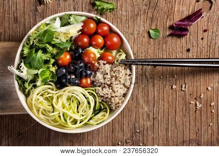 high angle view of an appetizing buddha bowl, made with lettuce, cornsalad, quinoa, zucchini spaghetti, blueberries and cherry tomatoes on a rustic wooden table