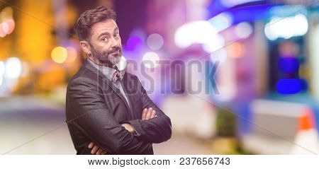 Middle age man, with beard and bow tie with crossed arms confident and happy with a big natural smile laughing at night club