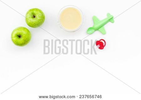 Fruit Puree For Baby. Jar With Food Near Apple, Pacifier, Toys On White Background Top View.