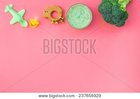 Healthy Food For Little Baby. Vegetable Puree With Broccoli Near Pacifier And Toys On Pink Backgroun