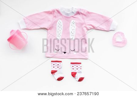 Newborn Baby's Background. Clothes For Small Girl With Booties On White Top View