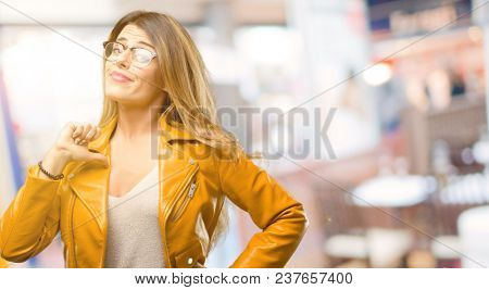 Beautiful young woman proud, excited and arrogant, pointing with victory face at restaurant