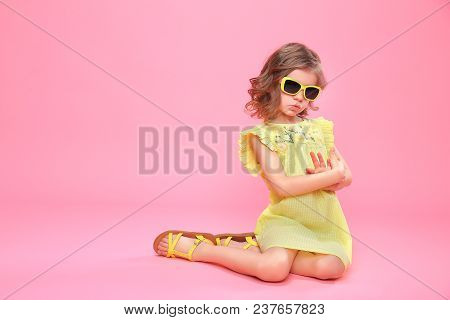 Wonderful Happy Girl In Yellow Dress And Sunglasses Sitting On Pink Backdrop.