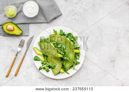 Spinach Pancakes With Spinach Leaves And Avocado Slices On Plate On Grey Background Top View.