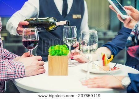Professional Waiter In Uniform Serving Wine To Guests Of Event. Catering Or Celebration Concept. Ser