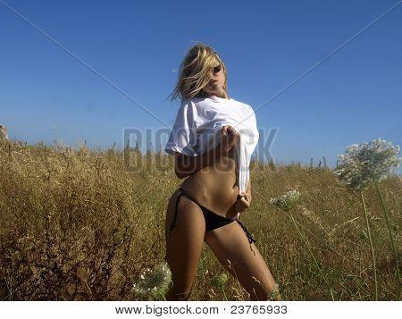 Blondine in schwarzen Bikini im Feld
