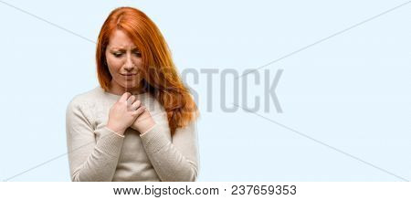 Beautiful young redhead woman crying depressed full of sadness expressing sad emotion isolated over blue background