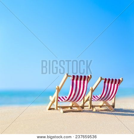 Two Striped Red-white Sunbeds At Sandy Tropical Ocean Beach In Hot Sunny Day. Natural Travel Backgro