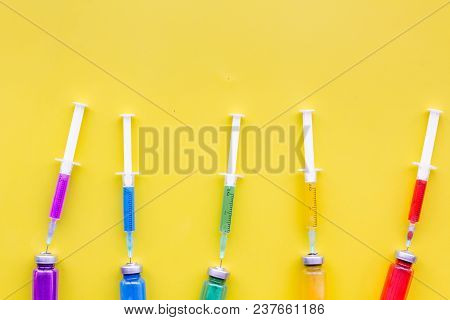 Vaccination, Immunization. Syringe And Bottle With Medicament On Yellow Background Top View.