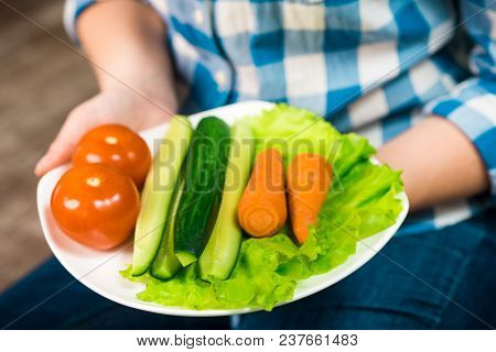 Girl With A Plate Of Vegetables In Hands. Healthy Eating Concept. A Girl In Jeans And A Plaid Shirt.