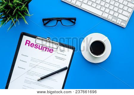 Empoyment Concept. Resume On Blue Work Desk With Coffee, Glasses, Keyboard Top View.