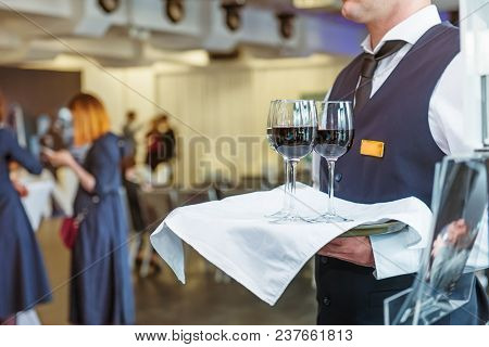 Professional Waiter In Uniform Holding A Tray With Glasses Of Vine At Business Event. Catering Or Ce