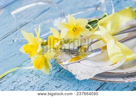 Set Of Tableware And A Bouquet Of Yellow Narcissus